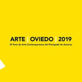 Detalle de la imagen gráfica de Feria Arte Oviedo 2019 donde se ve el título de la feria sobre un fondo amarillo, desde la parte izquieda del cuadrante se adentra un triángulo blanco que rompe la continuidad del fondo de color plano.