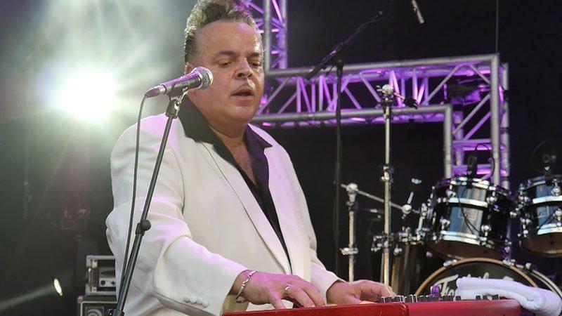 Foto de Mike Sanchez tocando en directo, sentado ante su teclado con su traje blanco característico y la pasión por la música en su cara.