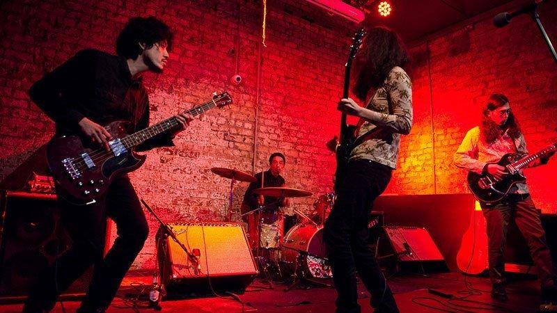 Foto de Minami Deutsch tocando en directo donde se ve a sus cuatro componentes dispersos a lo ancho del plano concentrados con sus instrumentos en un ambiente iluminado en rojo