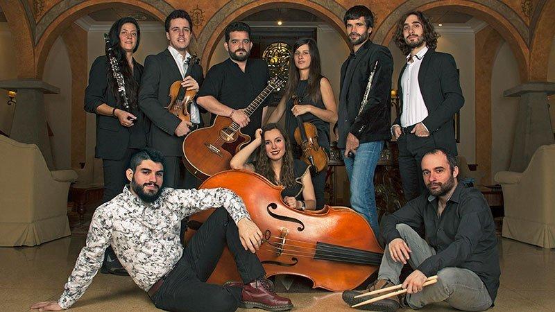 Foto de equipo de los nueve miembros de Quilombo Bacano posando en el hall de algún lujoso hotel, con cara de simpaticones y sus instrumentos entremezclados entre las personas.