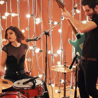 Foto de Escuchando Elefantes tocando en directo, a la izquierda se ve a Silvia sentada a la batería tocando con gesto enérgico, a la derecha se ve a Carlos, de pie a su lado, inclinando la guitarra también en una pose de máxima energía musical.