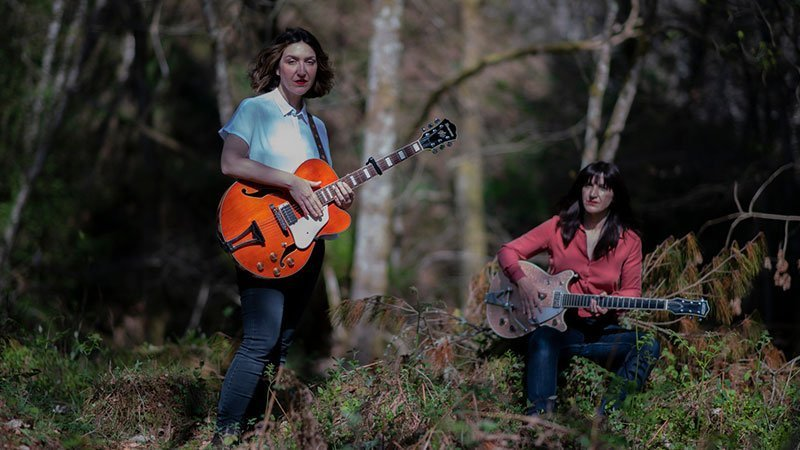 Foto de las hermanas Álvarez posando con sus guitarras en n bosque