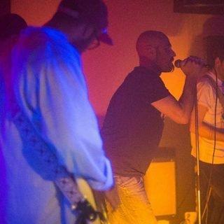 Foto de la banda Alpiste en directo, donde se ve al cantante agarrando el micro con amor, y al guitarra de costado tocando concentradísimo