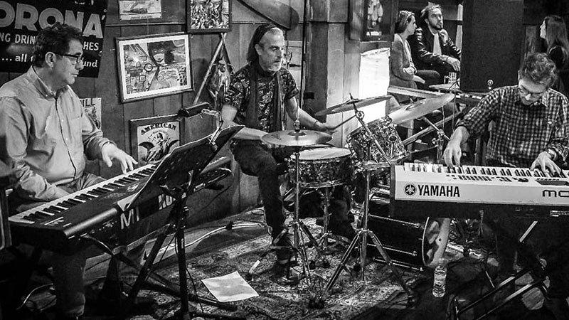 """Foto en blanco y negro del """"Nicolás Gorostidi Jazz Trío"""" tocando en directo en un bar."""