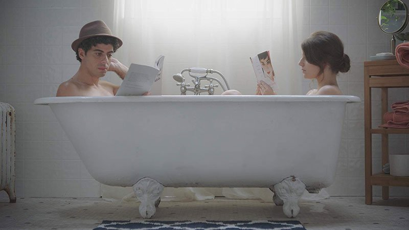 """Fotograma del corto """"The Art of Saying Goodbye"""" de Erika Sanz, en el que se ve a sus dos protagonistas metidos en una bañera, apoyados cada uno en un lado, el chico a la izquierda y la chica a la derecha, ensimismados leyendo cada uno un libro."""