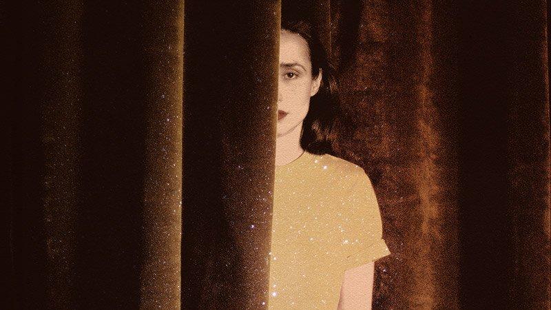 Detalle del cartel de la Gira de Teatros de Zahara en la que se ve una foto de ella asomándose entre las telas de un telón.