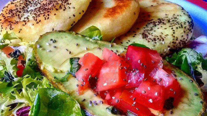 Foto detalle de un plato de arepas junto a brotes verdes y medio aguacate con tomate, todo salteado con semillas de Chía.