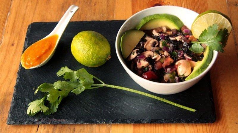 Foto de un bol de ceviche nikkei de champiñones y algas sobre una bandeja de pizarra y junto a una lima, una rama de cilantro y una cuchara de salsa roja