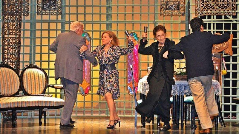 Foto de una escena de la obra en la que se ve a cuatro de los personajes bailando con gesto de felicidad y celebración