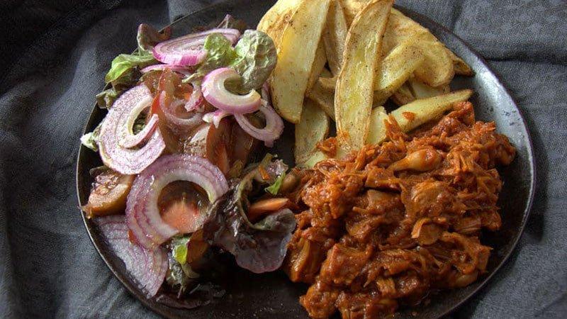 Foto de un plato de carne mechada de plátano con gajos de patata y ensalada, por Nahual Cocina.