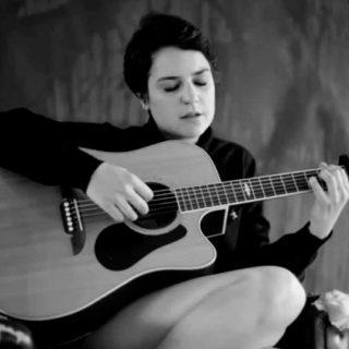 Cora Sayers con su guitarra acústica