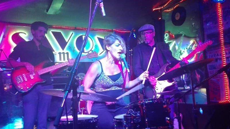 Foto de los integrantes de Fernández tocando en el escenario del Savoy, donde se ve a Sofía Fernández en el centro, sentada ante su batería mientras canta con energía. Detrás suyo puede verse al bajista a la izquierda y al guitarrista a la derecha.