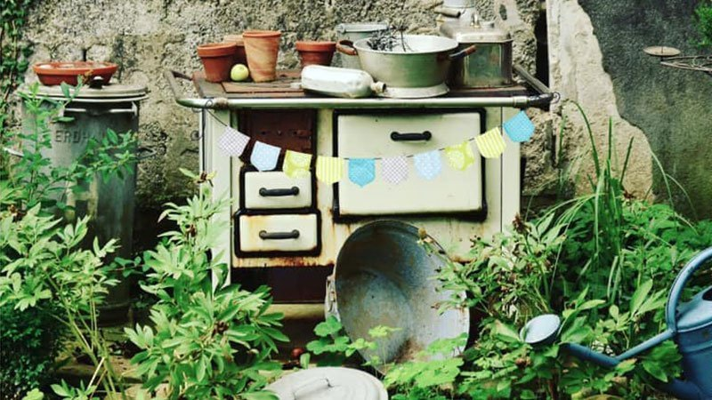 Detalle de la imagen del festival donde se ve una escena doméstica típica de las casas rurales con patio, se ve una antigua encimera de cocina con varios cajones y sobre ella varios utensilios como macetas, ollas, regaderas,...