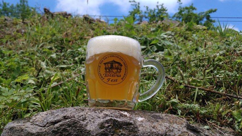 Foto de una jarra de cerveza con el nombre del festival impreso puesta sobre un muro de piedra, como tantos que hay en el pueblo de Tolivia, y con fondo verde de vegetación y cielo azul