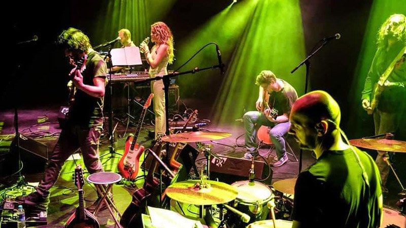Foto de Tubular Tribute tocando en directo, donde se ve, desde un lateral, a sus seis miembros repartidos por el escenario concentrados en sus instrumentos.