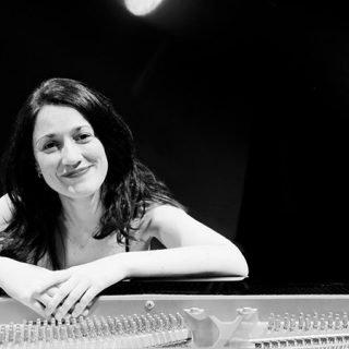 Foto en blanco y negro de Noelia Rodiles apoyada en un piano de cola.