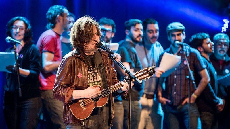 Foto de Nacho Vegas en el primer plano tocando un ukelele y el coro Al altu la lleva de fondo