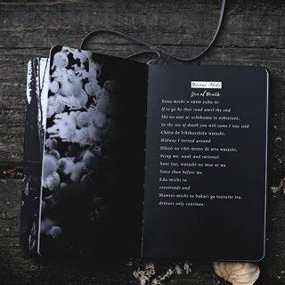 Libro negro con poema sobre mesa de madera