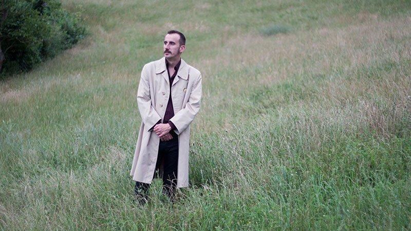 Foto de Pablo García (aka Pablo und Destruktion) vestido con gabardina en medio de un prao verde con pose pensativa mirando al infinito de la izquierda