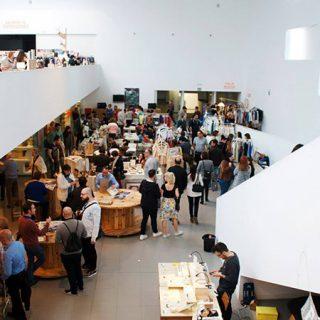 Foto de una edición anterior de LABshop donde se ve el hall de LABoral Centro de Arte lleno de puestos del mercadillo y abarrotado de gente