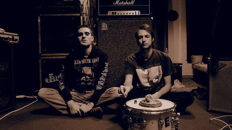 Foto de los miembros de Opium/Absinth sentados en en suelo ante sus amplificadores