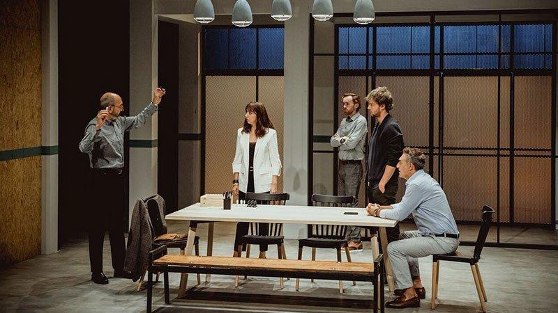 Foto de una escena de la obra de teatro 7 años en la que se ve a los cinco personajes dispuestos alrededor de una mesa discutiendo con gestos grandilocuentes