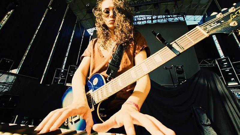 Foto de Alice Wonder tocando los teclados mientras su guitarra cuelga de su hombro