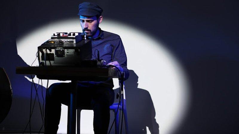 Foto de Ignacio Córdoba en directo sentado ante su aparato de generar atmósferas sonoras