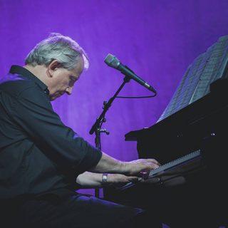 Foto de Wim Mertens visto de costado tocando y sintiendo el piano