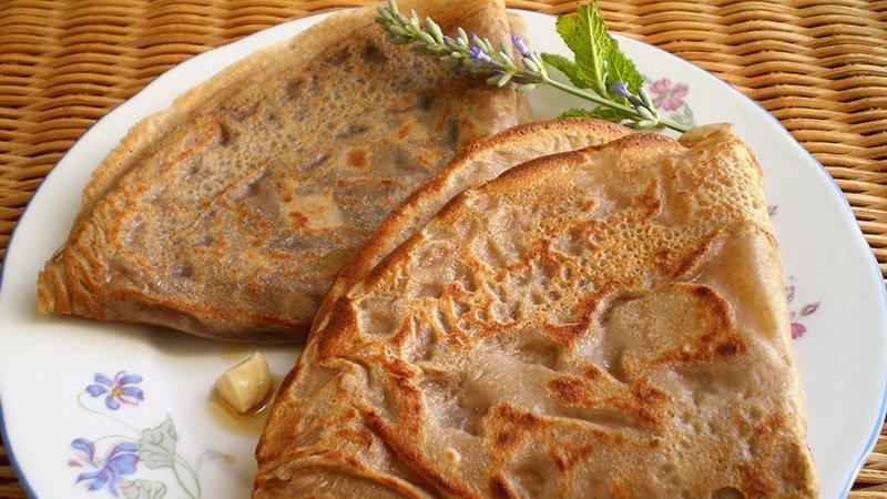 Foto de unos crepes bretones sobre un plato blanco y este sobre una cesta de mimbre, todo muy francés.