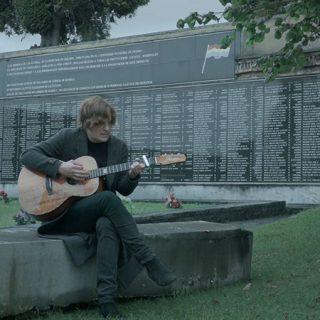 Fotograma del documental Cantares de una revolución en el que se ve a Nacho Vegas tocando la guitarra ante una fosa común