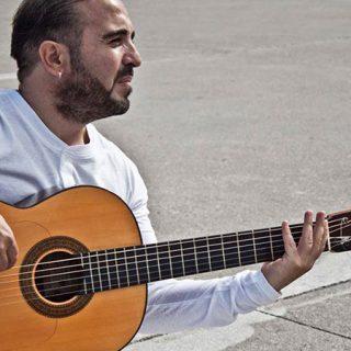 Foto de Francis Ligero cantando y tocando una guitarra