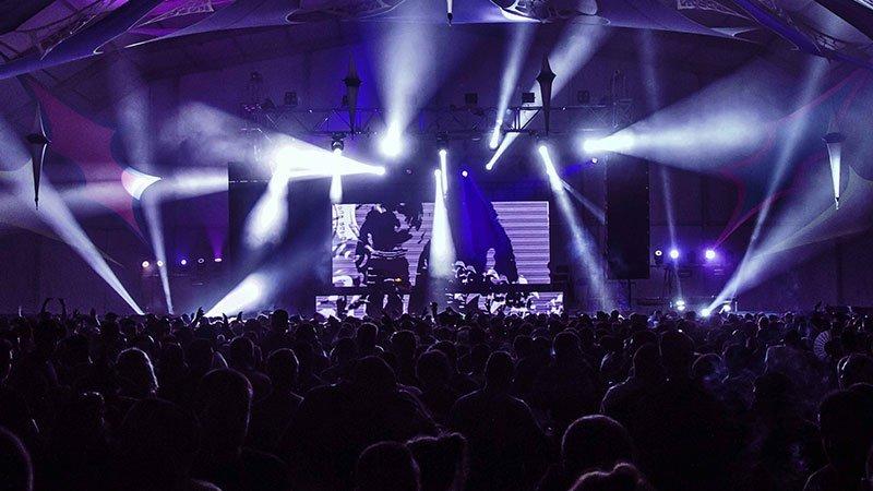 Foto de concepto de un escenario de música electrónica con luces y el público vibrando