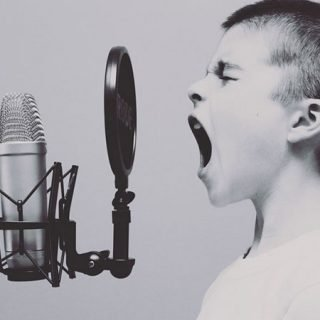 Foto de concepto en la que se ve un niño gritando a un micrófono