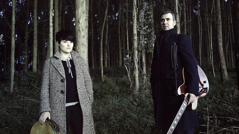 Foto de los componentes del dúo L-R posando ante un bosque de eucaliptos