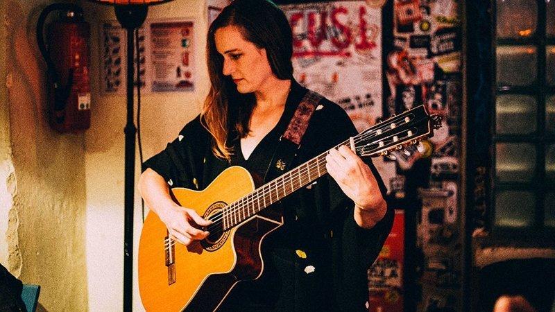 Foto de Laura Gibson en directo con su guitarra