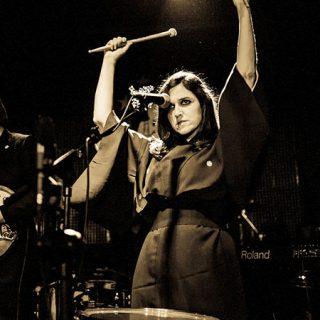 Foto de la banda tocando en directo, con su cantante, teclista y fundadora Svali en primer plano