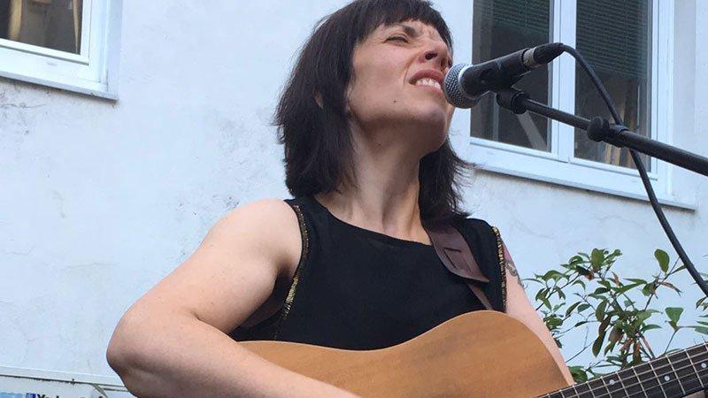 Foto de Astrogirl cantando y tocando la guitarra en uno de sus directos