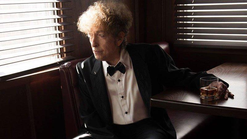 Foto de Bob Dylan mirando al infinito con un vaso de whisky en la mano