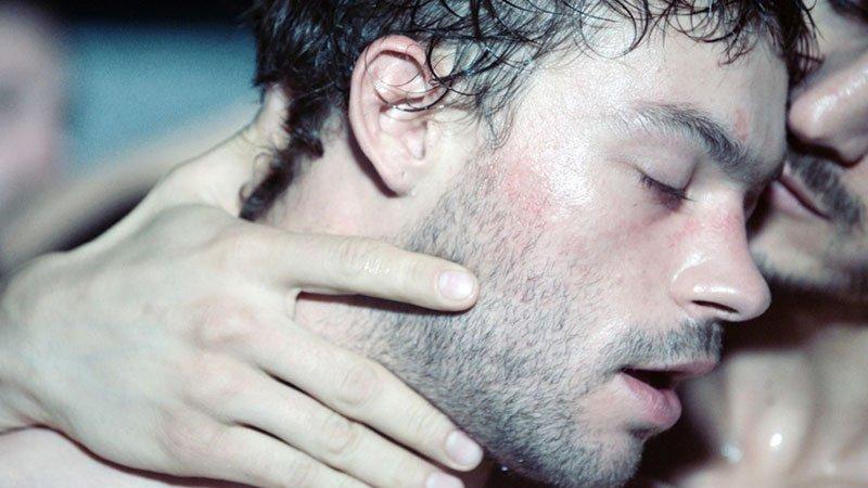 Fotograma de la película Sauvage donde se va a su protagonista en primer plano siendo abrazado por uno de sus clientes