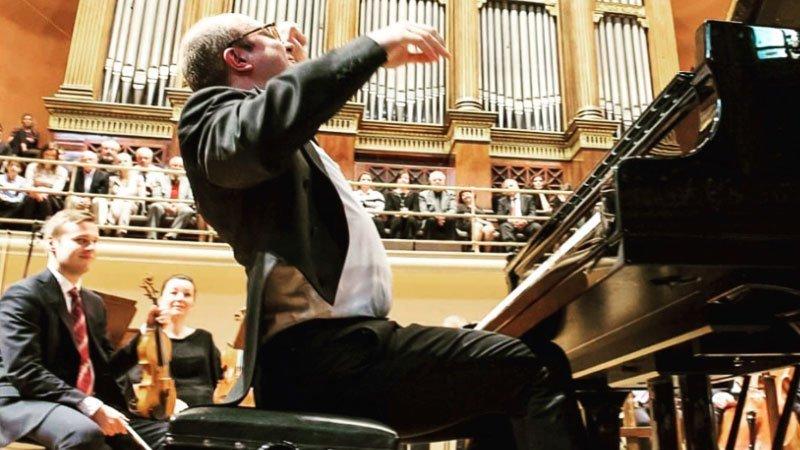 Foto de Alexander Gavrylyuk sentado ante el piano y alzando las manos justo antes de imprimir todo su arte sobre las teclas junto a una orquesta sinfónica