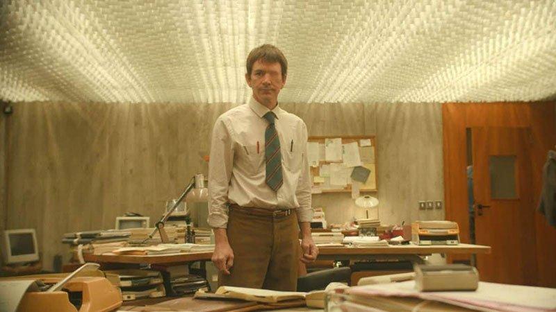 Fotograma de la película Au poste! donde se ve al protagonista de pie en una oficina y se observa que le falta un ojo