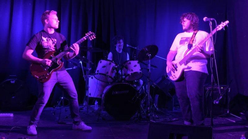 Foto de los tre componentes de Benedict Crow tocando en directo en el escenario de la Lata de Zinc