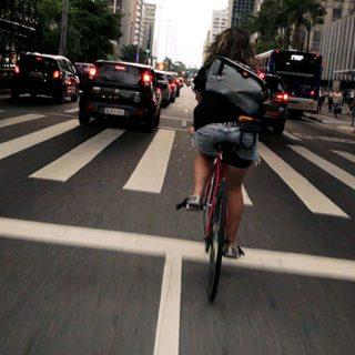 Fotograma del documental Bikes vs Cars en el que se ve desde atrás a una chica circulando por la calle en bicicleta rodeada de coches