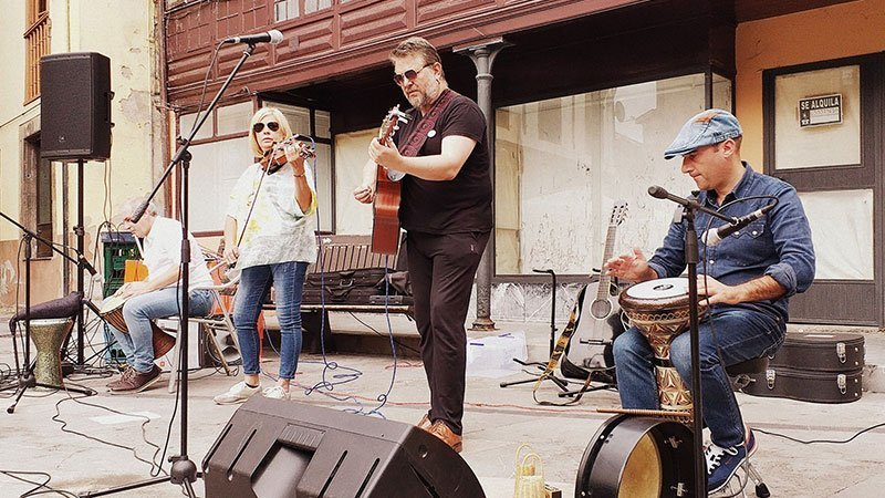 Foto de los miembros de la banda tocando en un concierto en la calle.