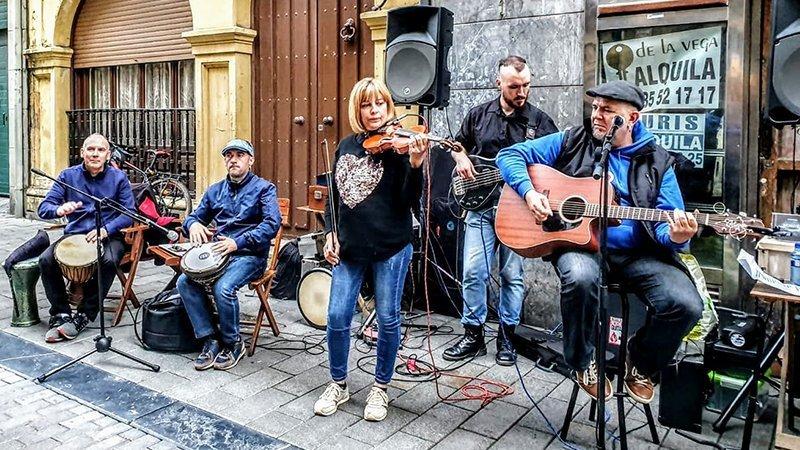 Foto de los miembros de la banda tocando en la calle en un concierto en Avilés