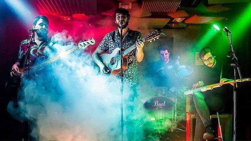 Los 4 miembros de Gente Terrible tocando en directo entre humo y luces de colores.