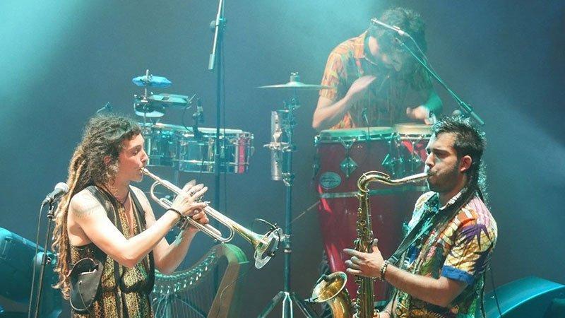 La Jari tocando en directo, se ve a la saxofonista y al trompeta en primer plano y al percusionista de fondo
