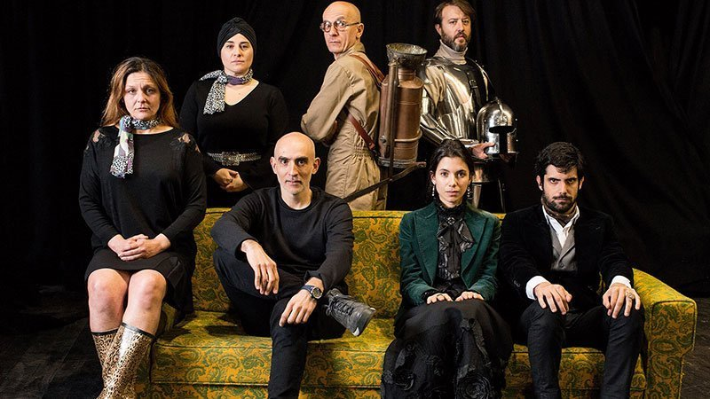Fotografía promocional de la obra La Valentía donde se presenta a sus 7 personajes sentados en un sofá mirando a cámara