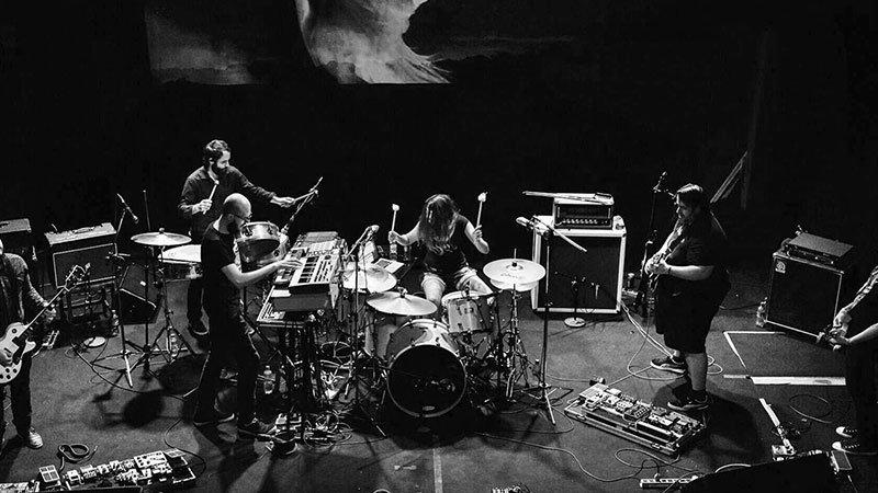 Foto de los miembros de Labirinto tocando en directo con la batería en el centro y el resto de músicos dispuestos alrededor con sus instrumentos